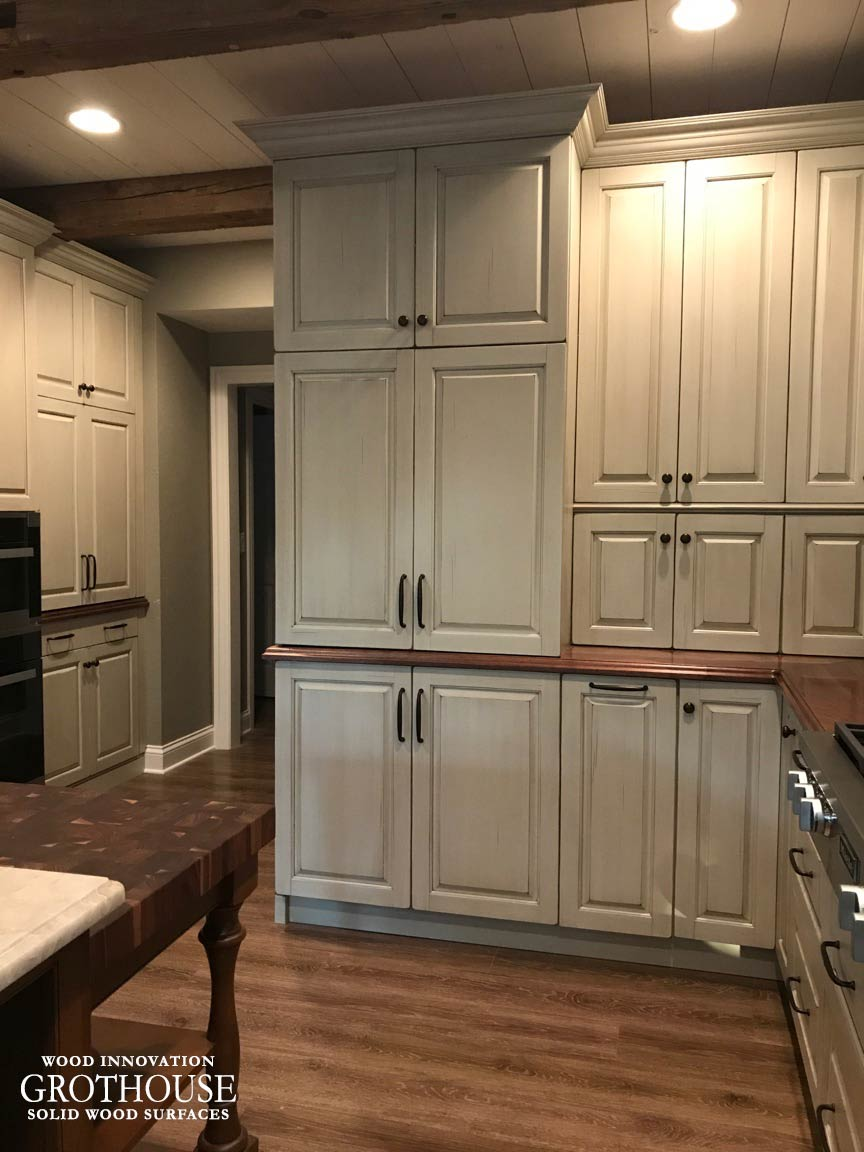Distressed walnut wood counters paired with gray kitchen cabinetry and a butcher block in Mapleton Illinois