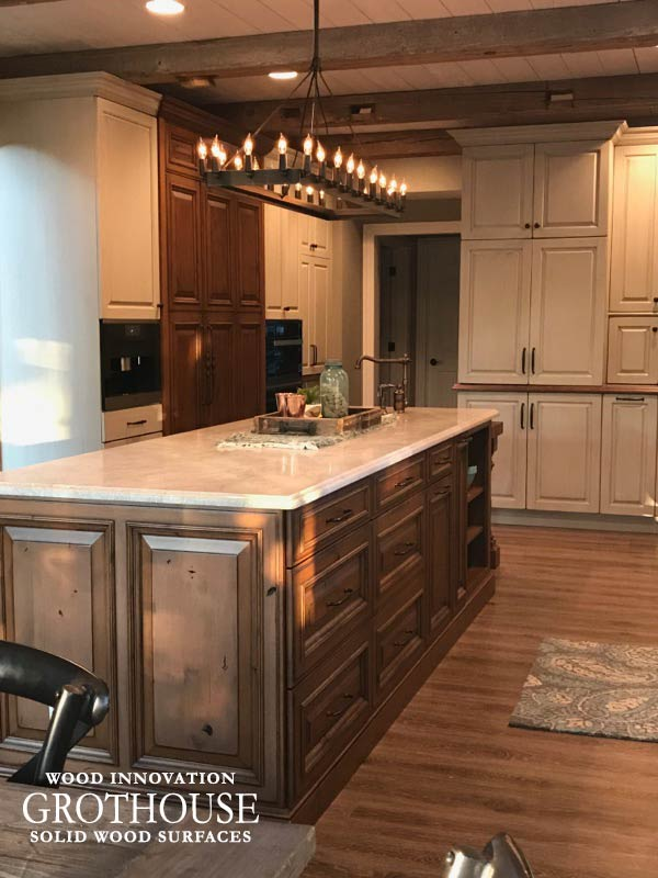 Kitchen island with a white countertop with undermount sink and distressed wood cabinets in Mapleton Illinois