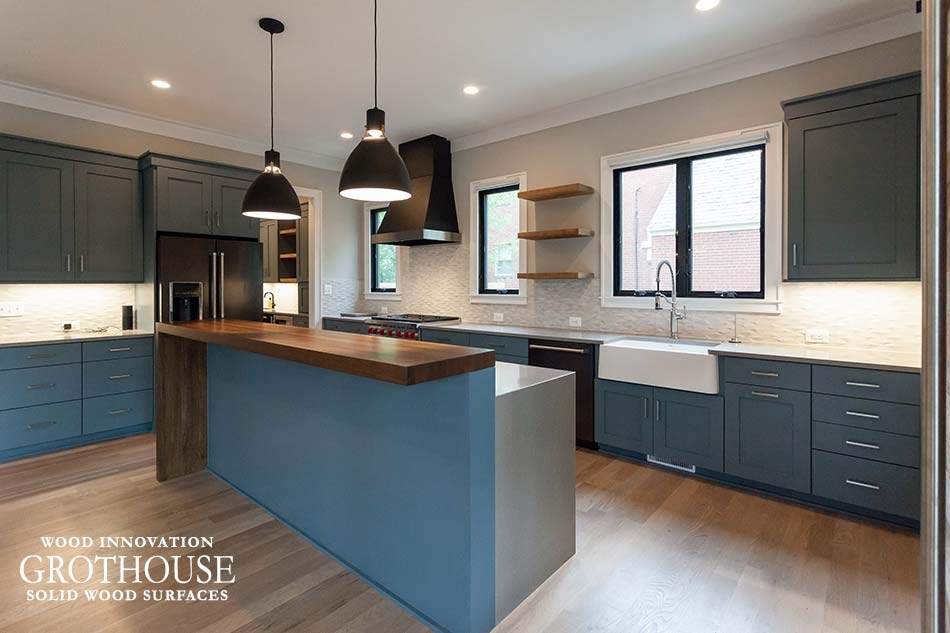 Transitional kitchen design with a rift white oak waterfall countertop, blue cabinetry and a farmhouse sink