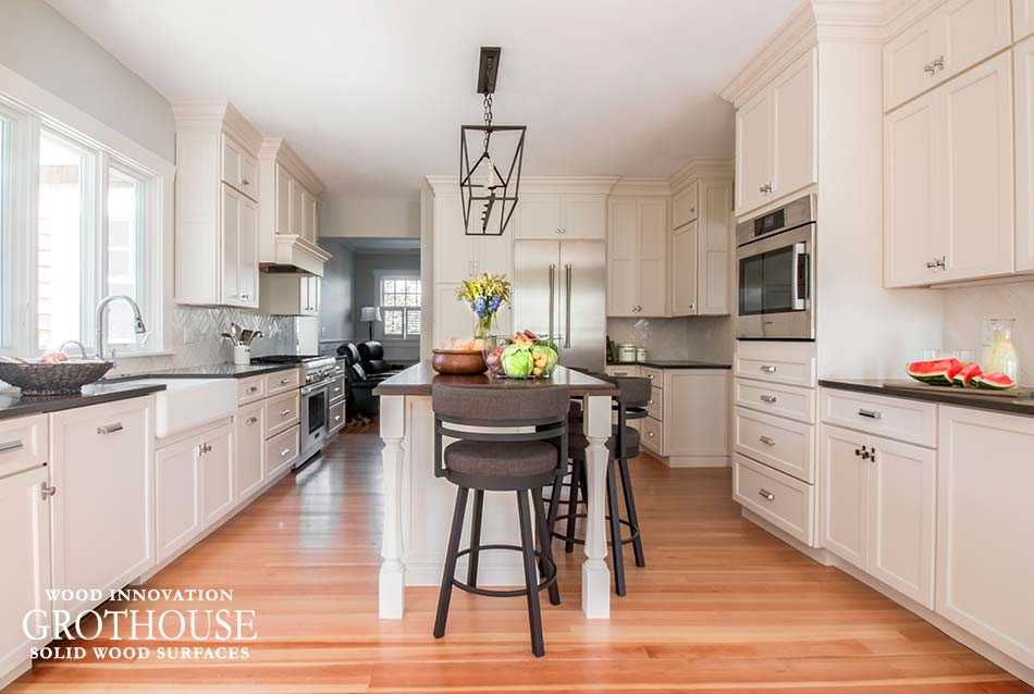walnut wood island counter with antique white cabinetry designed by the cabinetry kitchen and bath studio