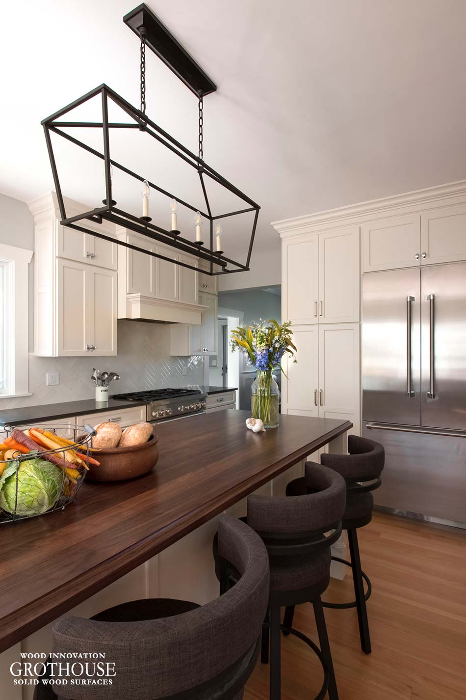 A Walnut wood island counter with kitchen island lighting and three kitchen island barstools