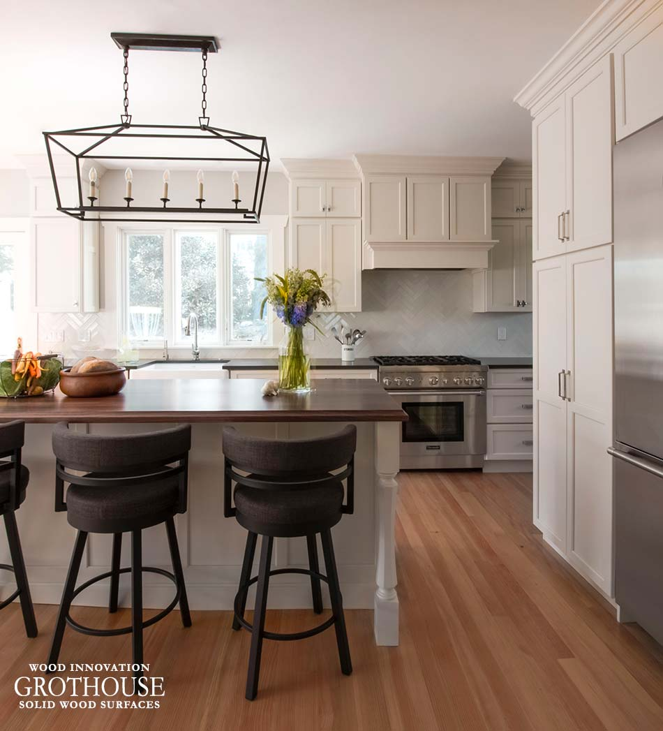 Traditional kitchen design with a walnut wood island counter and antique white perimeter cabinetry and rangehood