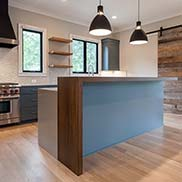 Rift white oak waterfall countertop on a kitchen island with blue perimeter cabinetry and wolf appliances