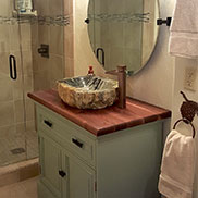 walnut with sapwood bathroom vanity top in a traditional bathroom design with blue cabinets in Florida