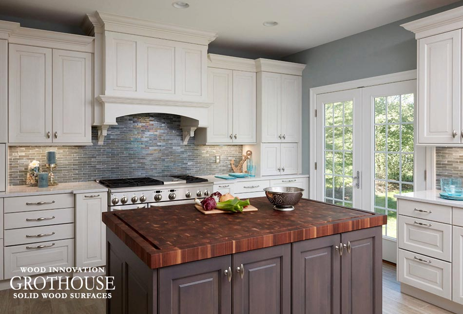 Large Cooking Range with a Walnut Checkerboard Island Countertop Across From it in a Traditional Kitchen