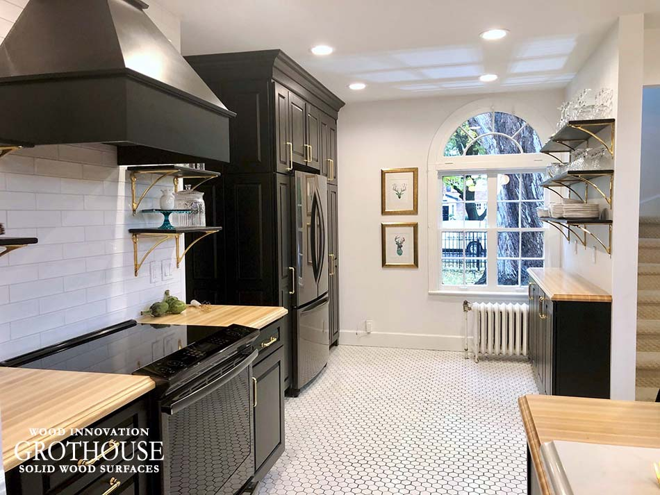 Ash Wood Kitchen Countertops with Black Kitchen Cabinetry, Floating Shelves and Brass Hardware and Fixtures