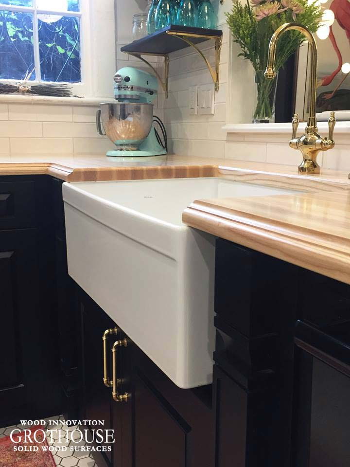 White Farmhouse Sink Surrounded by Ash Wood Kitchen Countertops in a Traditional Kitchen Design in Michigan
