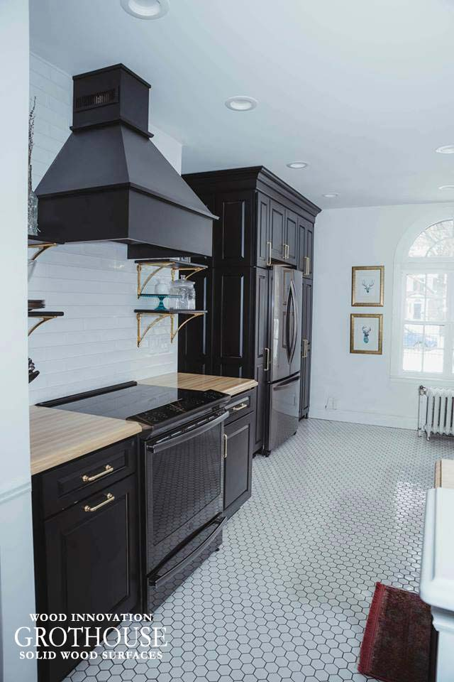 Ash Wood Kitchen Countertops Surrounding a Cooking Range Area with Black Cabinetry and Brass Hardware