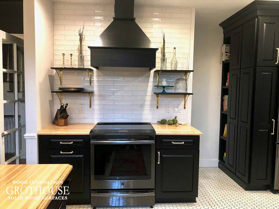 Ash Wood Kitchen Countertops Around Stainless-Steel Range with a Black Custom Rangehood and Floating Shelves