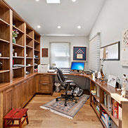 Large Walnut Office Desk Complemented with Matching Cabinetry and Open Shelving for an Office in California