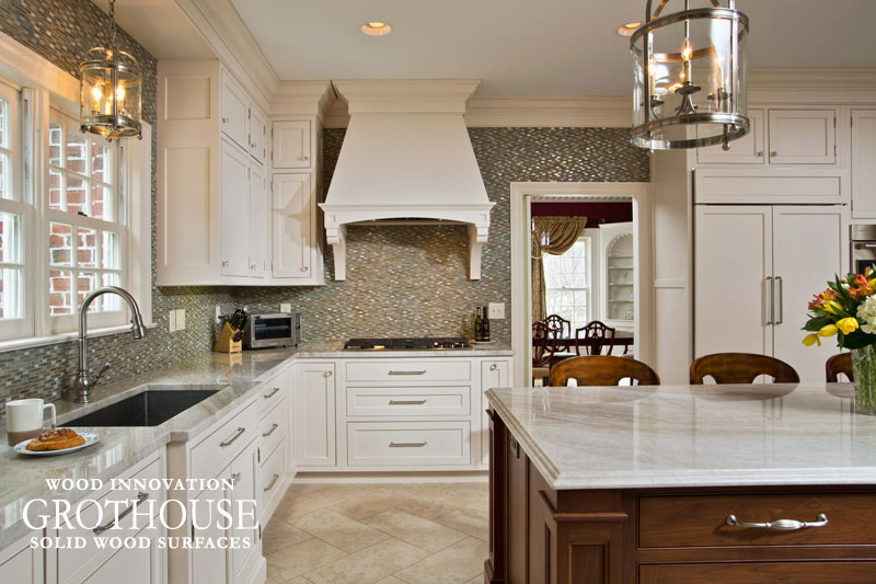 White Cabinetry with a Walnut Sapwood Kitchen Countertop and Taj Mahal Quartzite Countertops in Saratoga Springs