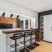 Custom Walnut Wood Waterfall Table with a Waterproof Finish in a Contemporary Kitchen Design in Longwood, Florida