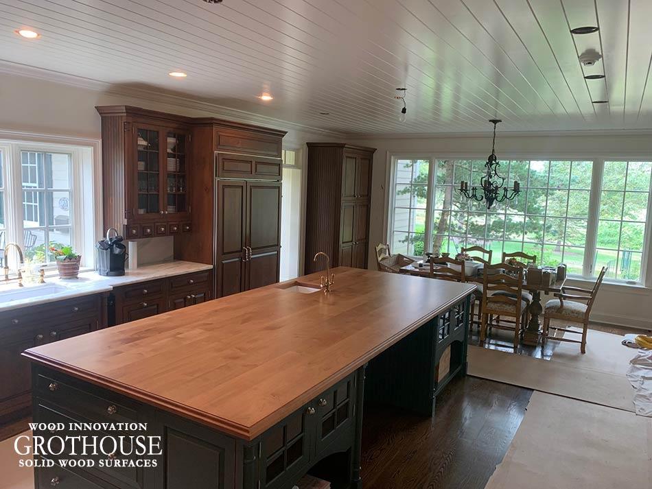 Alder Wood Kitchen Island Countertop with Dark Blue Kitchen Island Cabinetry in a Traditional Kitchen Design