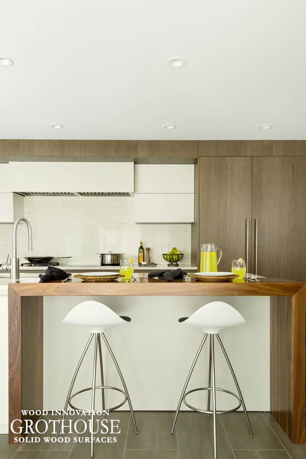 Walnut Waterfall Island Table with White Barstools in a White Kitchen in Roslyn, New York